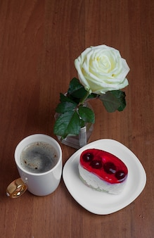 A cup of coffee with a cake and a rose