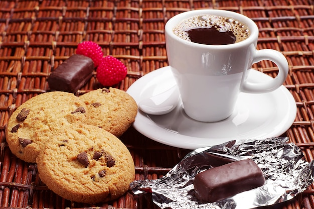 Cup of coffee with chocolate candy and cookies