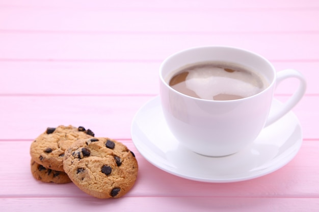 Cup of coffee with chocolate cookies on pink background