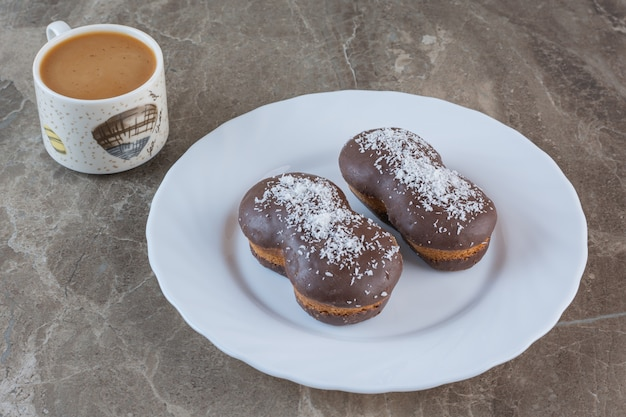 Cup of coffee with chocolate cookies on white plate.