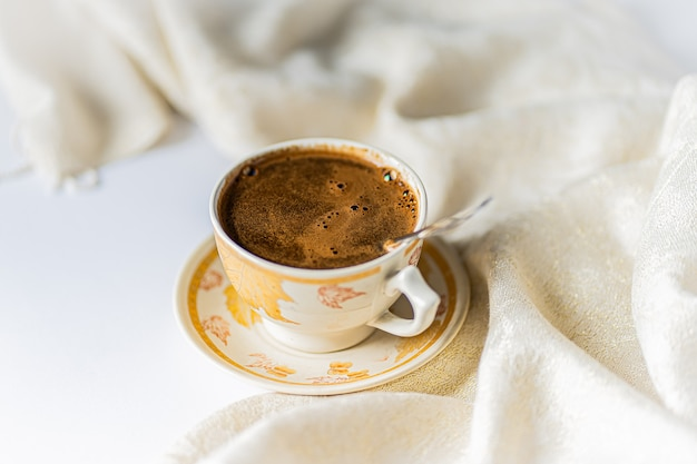 Cup of coffee with chocolate on a light white table and beige napkin