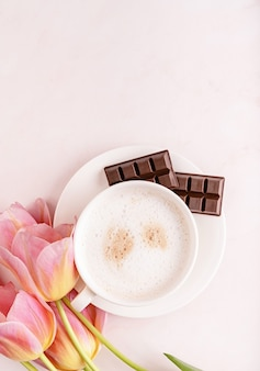 Cup of coffee with chocolate and pink tulips top view on marble background