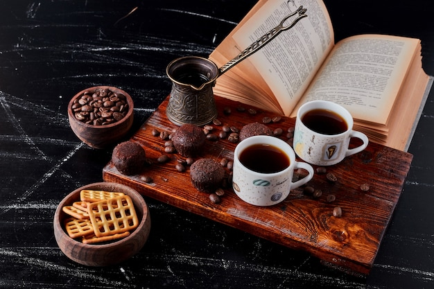 A cup of coffee with chocolate pralines and cookies.