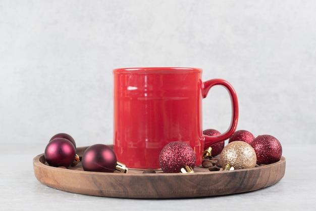 Tazza di caffè con ornamenti natalizi sul piatto di legno