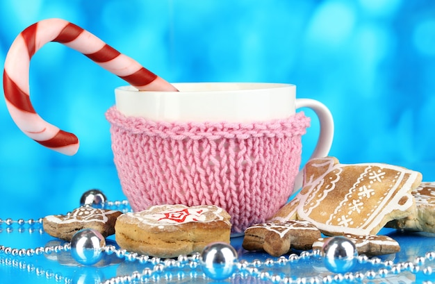 Cup of coffee with christmas sweetness on blue background