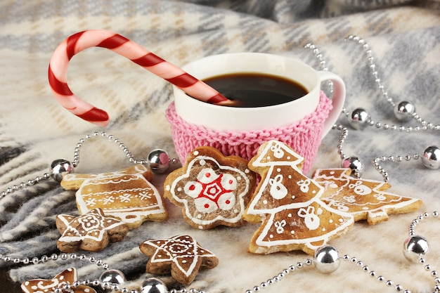Cup of coffee with christmas sweetness on plaid close-up