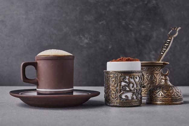 Una tazza di caffè con cannella in polvere intorno.