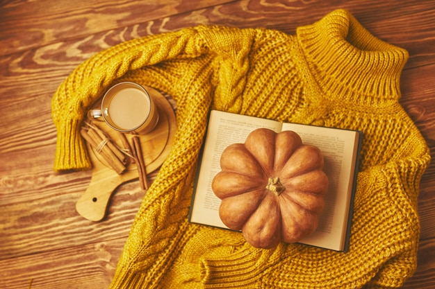 Cup of coffee with cinnamon and pumpkin on wooden table with book and sweater