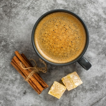 Cup of coffee with cinnamon stick and turkish delight on grey background. top view