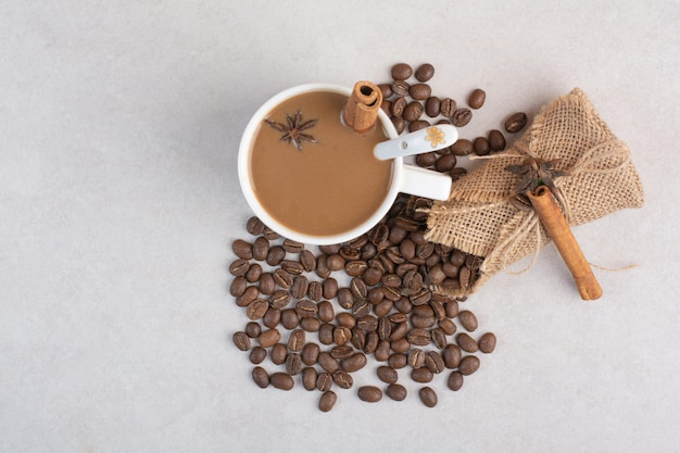 A cup of coffee with cinnamon sticks and coffee beans on marble background. high quality photo