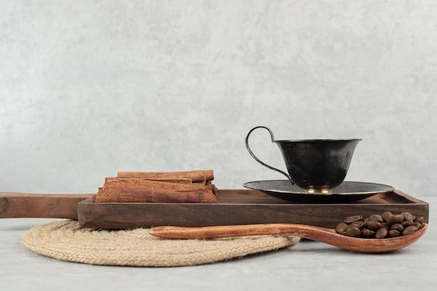 Tazza di caffè con bastoncini di cannella su tavola scura e chicchi di caffè