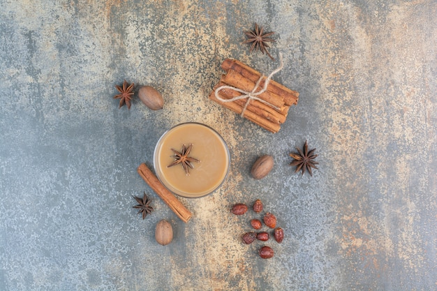 Cup of coffee with cinnamon sticks on marble background. high quality photo
