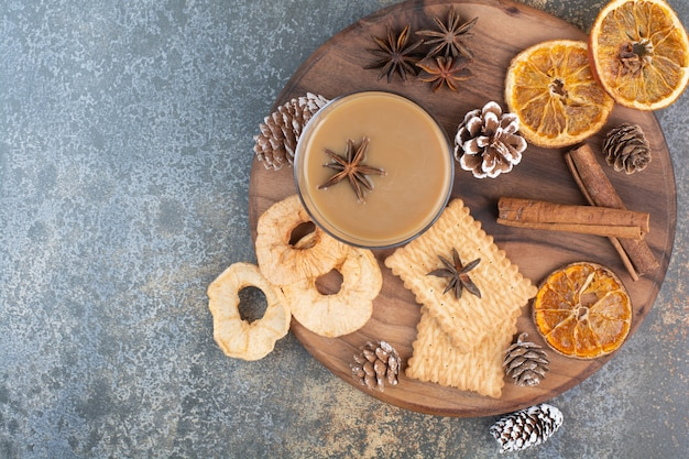 Cup of coffee with cinnamon sticks and pinecones on wooden plate. high quality photo