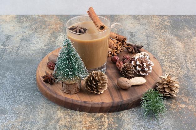 Tazza di caffè con bastoncini di cannella e pigne nelle quali sul piatto di legno. foto di alta qualità