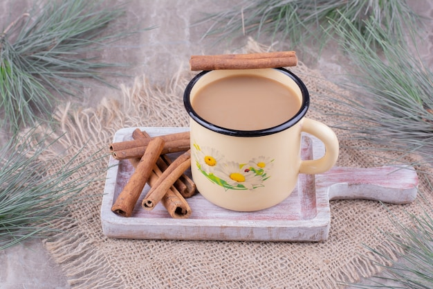 A cup of coffee with cinnamon sticks on rustic wooden board.