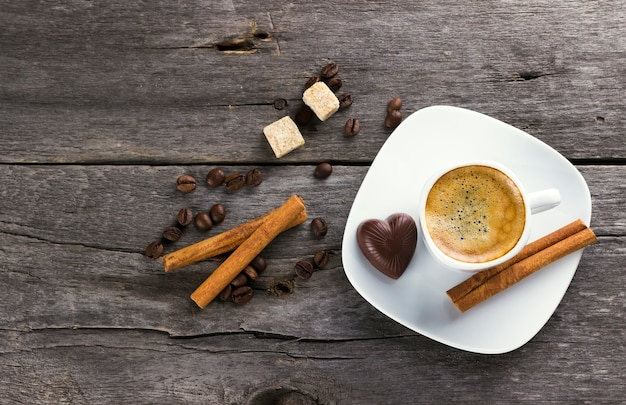 Cup of coffee with cinnamon and sugar on a wooden background