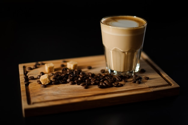 A cup of coffee with coffee beans and cane sugar on a wooden board.