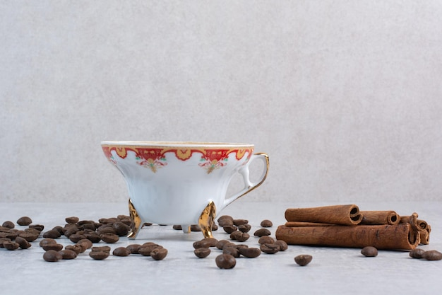 Cup of coffee with coffee beans and cinnamon sticks. high quality photo
