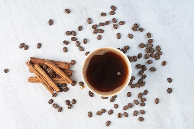 Tazza di caffè con chicchi di caffè e bastoncini di cannella. foto di alta qualità