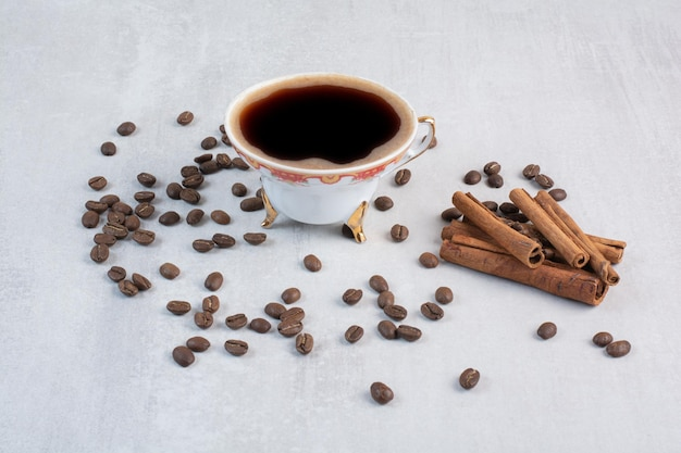 Cup of coffee with coffee beans and cinnamon sticks