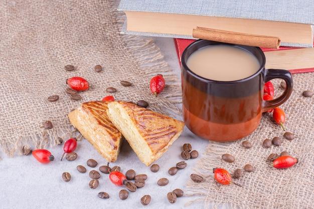 Tazza di caffè con chicchi di caffè e pasticcini su tela. foto di alta qualità