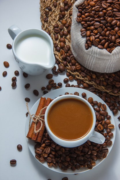 A cup of coffee with coffee beans in a sack and saucer, milk, dry cinnamon high angle view on a trivet and white surface