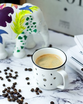 A cup of coffee with coffee beans on table
