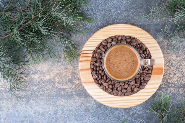 A cup of coffee with coffee beans on wooden board.