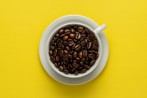 Cup of coffee with coffee beans on yellow surface.