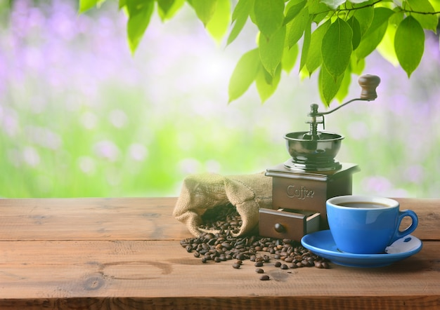 Cup of coffee with a coffee grinder on a sunny day