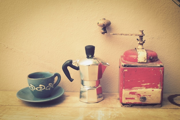 Cup of coffee with a coffee pot and a grinder