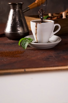 Cup of coffee with cooffee beans with grains of coffee and spices on a stone background