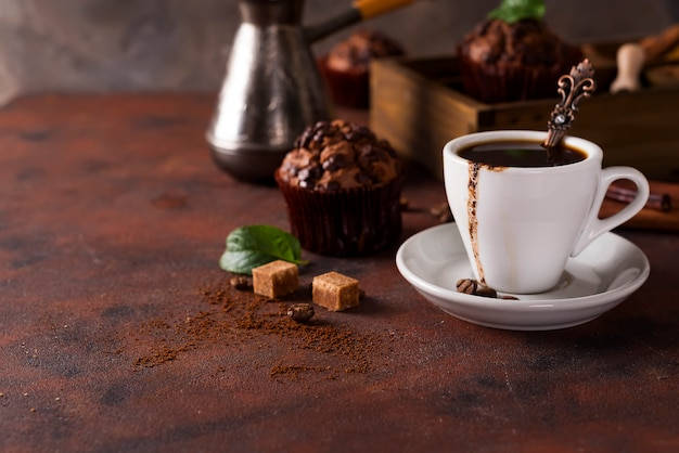 Cup of coffee with cooffee beans, wooden box with grains of coffee and spices,