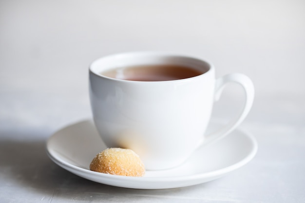 A cup of coffee with cookie on ceramic