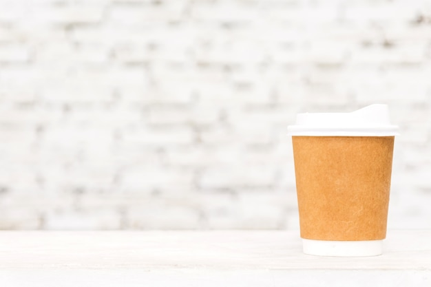 Cup of coffee with copy space on table against white brick wall background