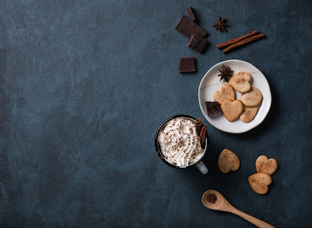 A cup of coffee with cream and chocolate chips  on a dark  table with homemade cookies, chocolate and cinnamon. top view, copy space and flat lay