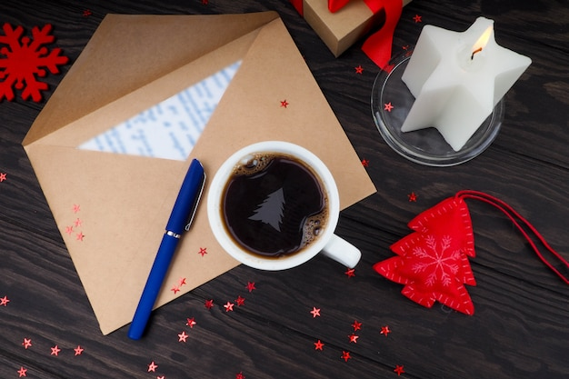 Cup of coffee with cream christmas tree on a table. letter to santa claus.