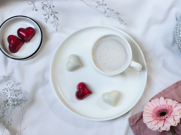 Cup of coffee with cream and excellent bonbons with a heart shape on a white bed. romantic breakfast in bed. flat lay, top view
