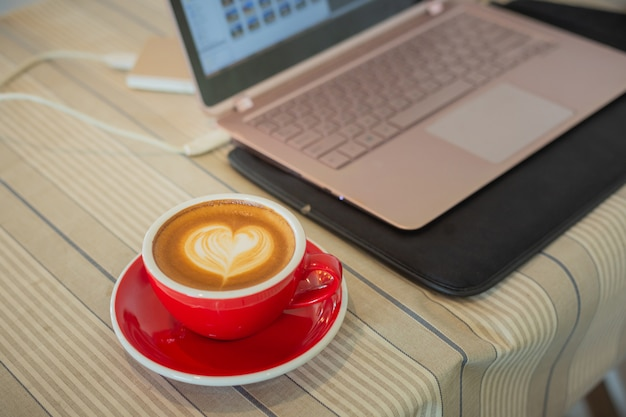 Cup of coffee with cream heart shape symbol near laptop computer on table
