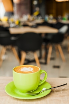Cup of coffee with creative latte art on wooden table at cafeteria