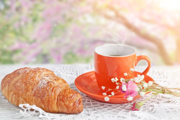 Cup of coffee with croissant on a table against the blossoming pink tree