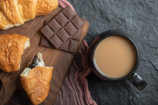 Una tazza di caffè con croissant e barrette di cioccolato.