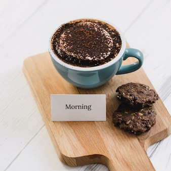 Cup of coffee with dark chocolate cookies and greeting message on wood platter in cafe