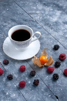 Cup of coffee with different berries on grey,  berry fruit coffee