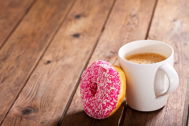 Cup of coffee with donut on wooden table