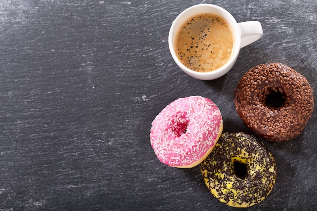Cup of coffee with donuts on dark table, top view