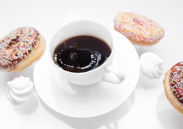 Cup of coffee with donuts and meringues in motion