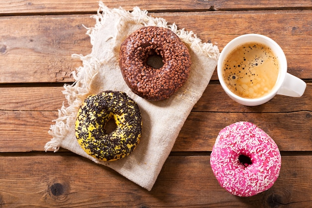 Cup of coffee with donuts on wooden table, top view