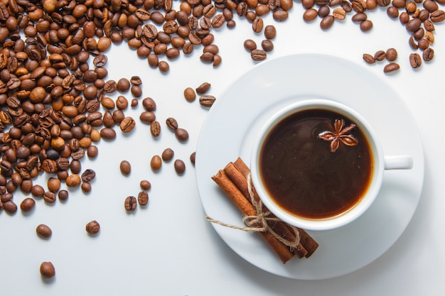 A cup of coffee with dry cinnamon top view with coffee beans on surface