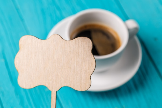 Cup of coffee with empty sign for wishes on blue wooden table